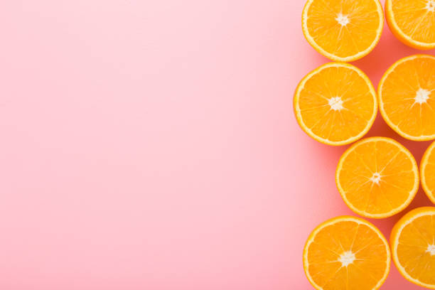 Bright halves of oranges. Fresh fruits. Empty place for text on light pink table background. Pastel color. Closeup. Top down view. stock photo