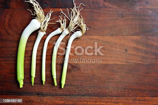 923629650istockphoto A bright horizontal click of five parallel white garlic bulbs with  roots bunch and shoots with light green shade over a dark brown wooden board surface 1096465160