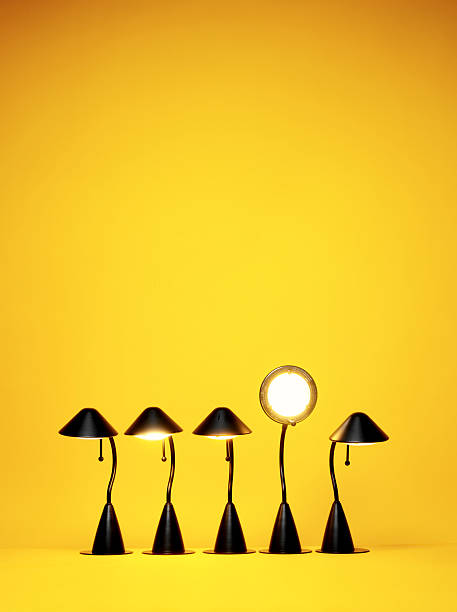 Bright Idea, Five desk lamps against yellow stock photo