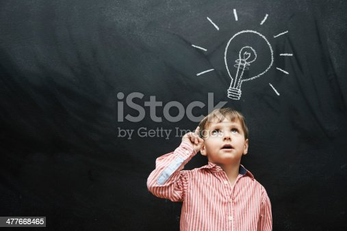 Studio shot of a young boy with a chalk drawing of a light bulb above his head