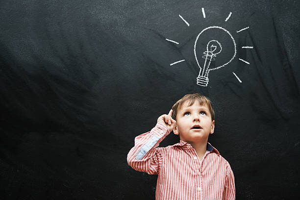 Bright ideas for a brighter future Studio shot of a young boy with a chalk drawing of a light bulb above his head child prodigy stock pictures, royalty-free photos & images