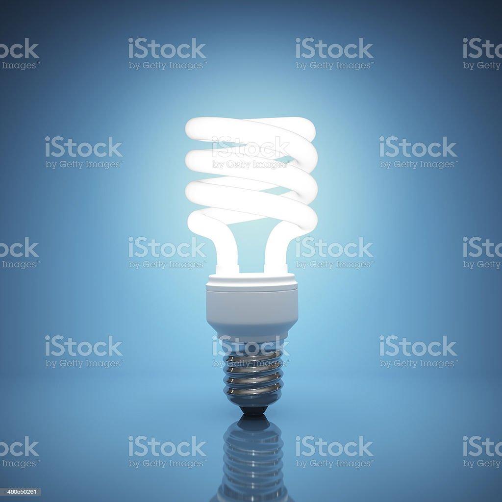 Bright, illuminated light bulb on blue background stock photo