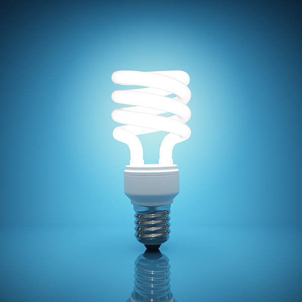 bright, illuminated light bulb on blue background - fluorescent light stock pictures, royalty-free photos & images