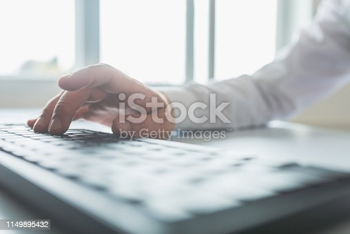 Bright image of a businessman typing on computer keyboard sitting by an office windows.
