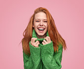Modern ginger woman cuddling in cozy green sweater and laughing at camera on pink background