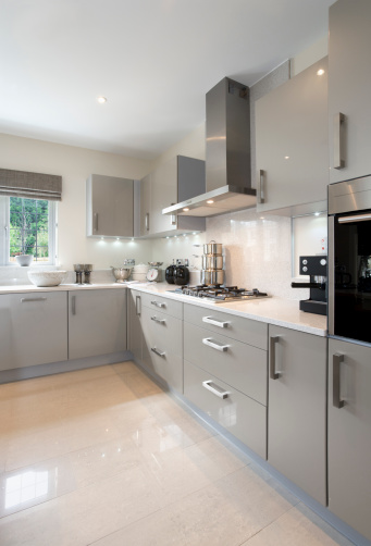a corner of a bright kitchen in an expensive new home. Colours are neutral tones of grey with brushed metal and a light cream granite worktop whilst the downlighting adds a hint of yellow and warmth to the scene. The window view is to a garden introducing a subtle splash of green.