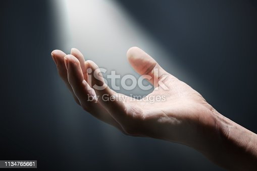 Bright light rays shihing on man's hand in darkness.