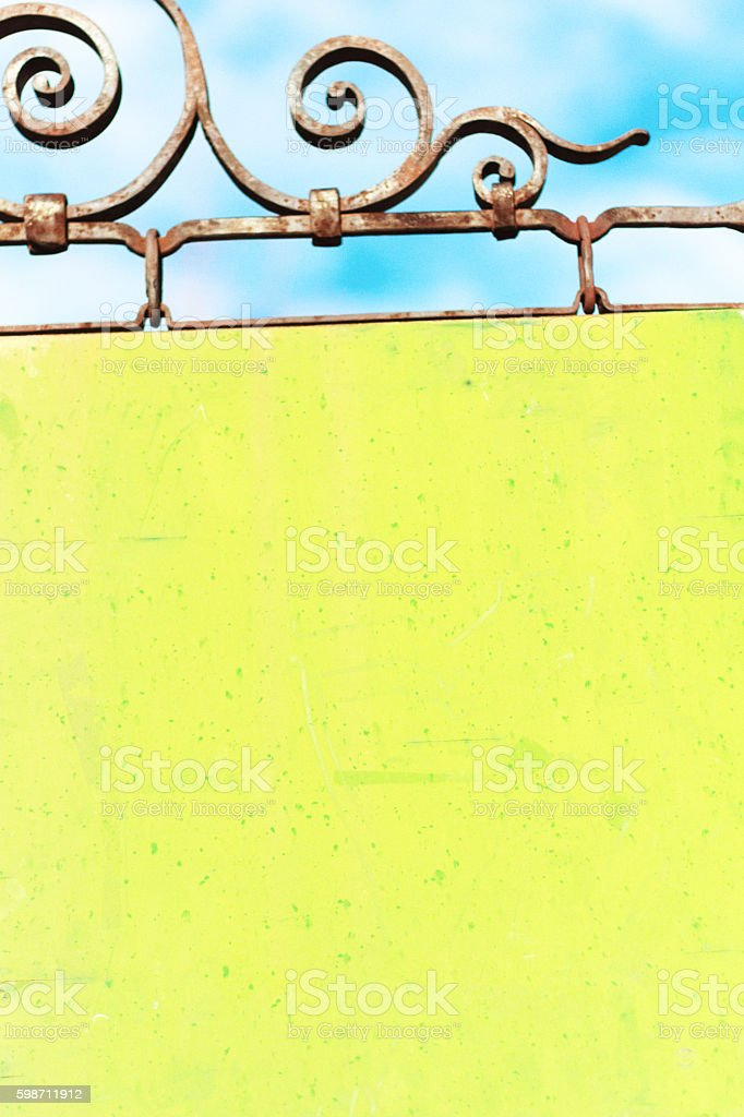 A bright lime green blank wooden sign hanging from antique scrolled...