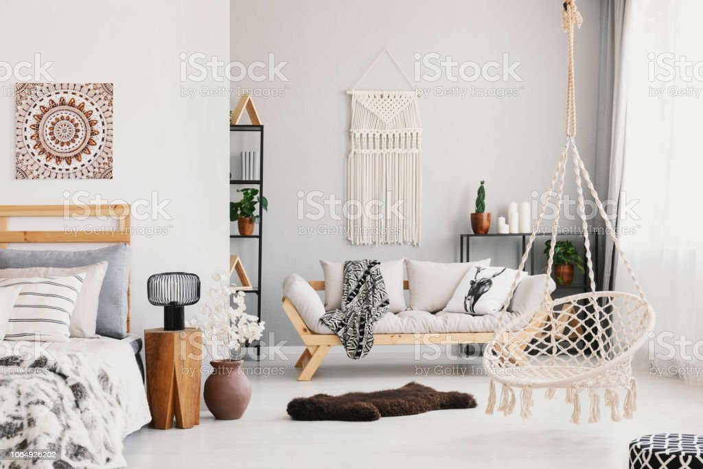 Bright living room interior with macrame on the wall, beige couch with pillow and blanket, hammock chair, fluffy rug and bedside table with lamp standing by the bed in the real photo – zdjęcie