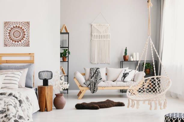 Bright living room interior with macrame on the wall, beige couch with pillow and blanket, hammock chair, fluffy rug and bedside table with lamp standing by the bed in the real photo stock photo