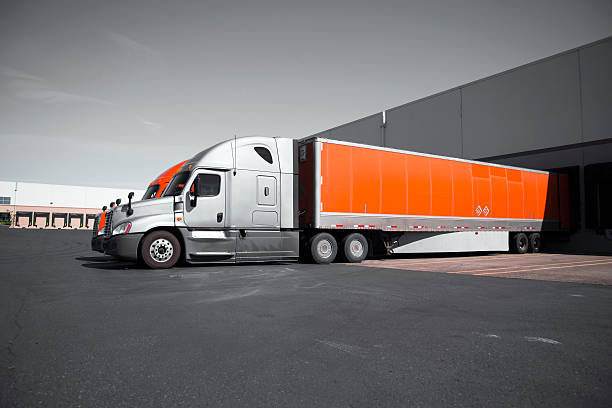 bright modern orange and gray semi trucks unloading in warehouse - lorries unloading stock photos and pictures
