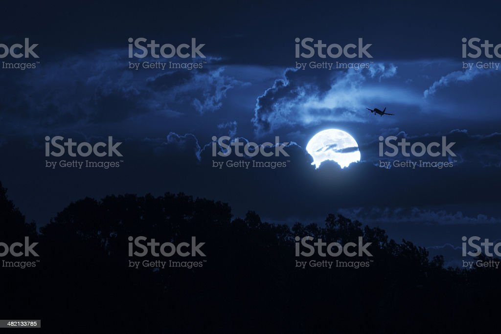 Bright Moon Illuminates The Sky And Approaching Commercial Jet Aircraft stock photo