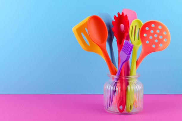 helle mehrfarbige Küchenutensilien auf blauem und lila Hintergrund mit Kopierraum – Foto