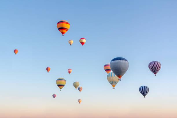 lumineux multicolores montgolfières volant dans le ciel sunsrise cappadoce - montgolfière photos et images de collection