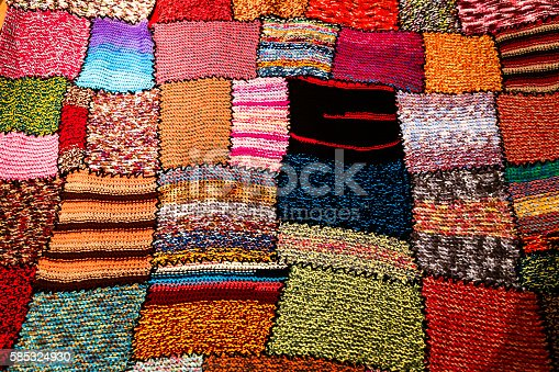 Close up image of a bright, multi-coloured handmade patchwork blanket or quilt, Each section is uniquely designed. Horizontal colour image.