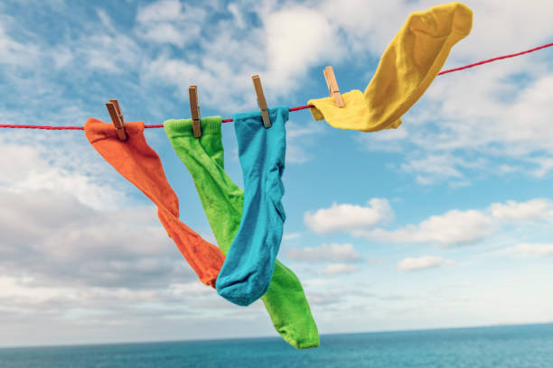bright multi-coloured socks on a washing line overlooking the sea. - washing line stock pictures, royalty-free photos & images