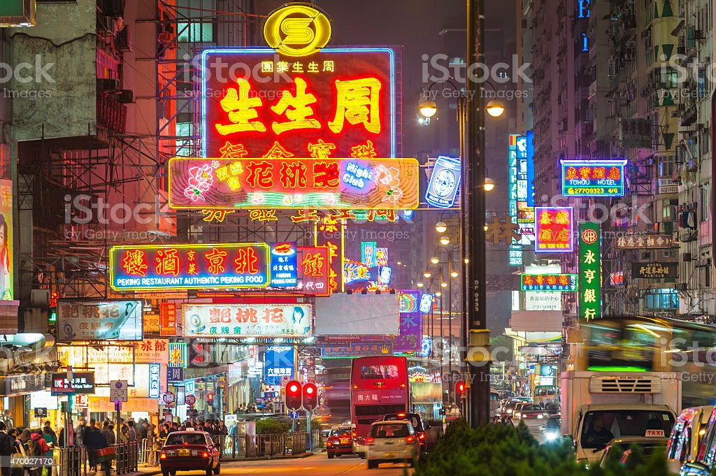 Bright neon signs colourful crowded cityscape Kowloon Hong Kong China Vibrant neon signs and bright street lights glowing above the busy night traffic of taxis, double decker buses and pedestrians along Nathan Road in the crowded Tsim Sha Tsui district of Kowloon, Hong Kong, China. ProPhoto RGB profile for maximum color fidelity and gamut. 2015 Stock Photo
