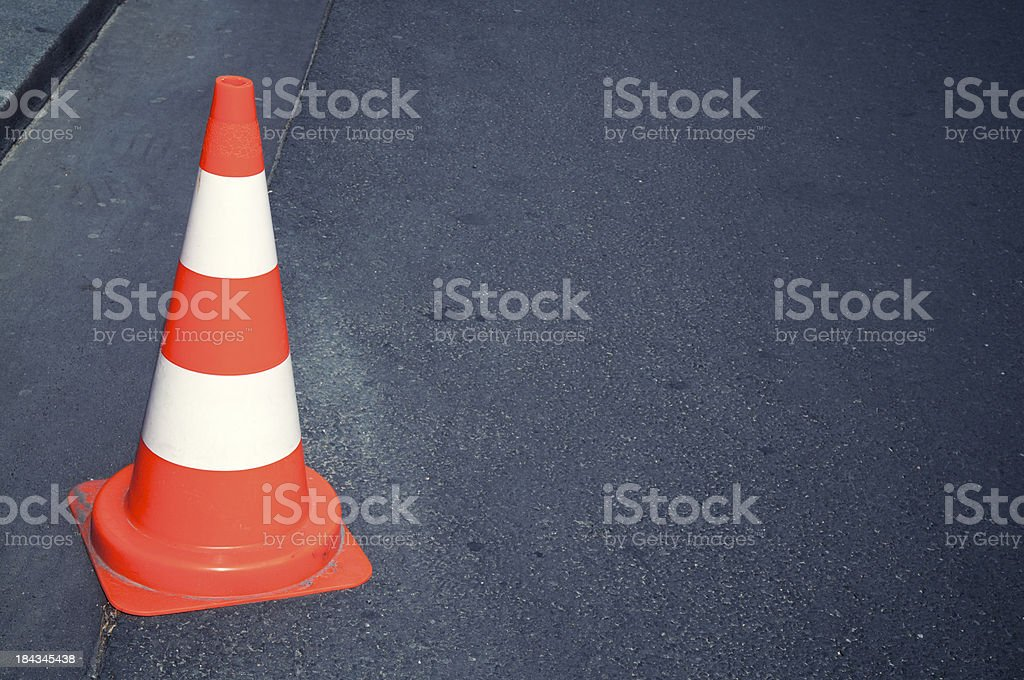 Bright orange and reflective white traffic cone sits at the edge of...