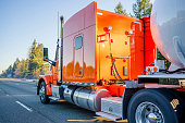 Bright orange big rig American professional long haul semi truck transporting tank semi trailer for transportation of liquid and liquefied chemical commercial cargo running on the road