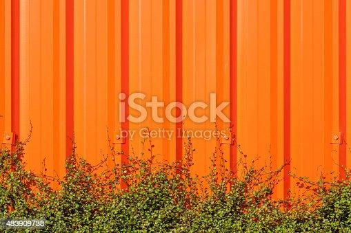 607593268istockphoto Bright orange corrugated painted metal wall background. 483909738