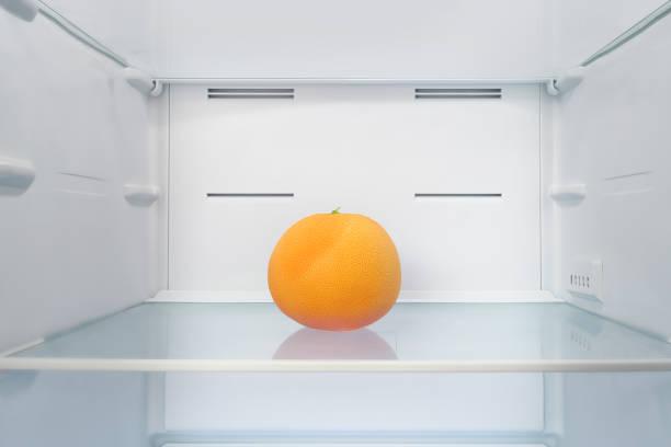 leuchtend orange grapefruit in kühlschrank - offene regale stock-fotos und bilder