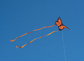 Bright orange monarch butterfly kite flys high on a windy spring day at kite festival.