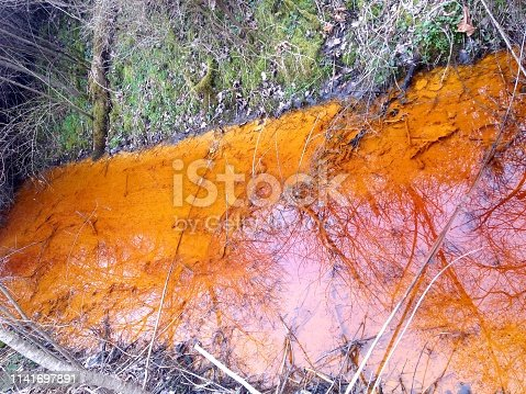 A stream is bright orange with run-off from acid mine drainage
