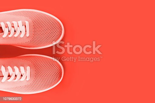 istock Bright orange sneakers on an orange background. 1079630372
