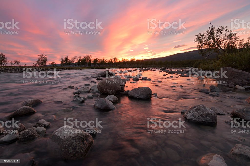 Bright orange sunset over wild river and orange reflection foto de stock royalty-free