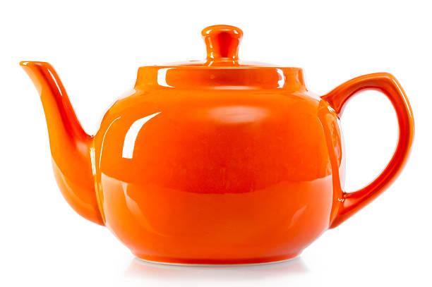 strahlend orange teekanne auf weißem hintergrund - keramikteekannen stock-fotos und bilder