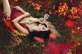 bright photo in burgundy shades, girl in dark dress color of Marsala, lady with dark hair lies on grass, fallen red and yellow leaves, barn owl spread its wings on sleeping fairy and protects sleep.