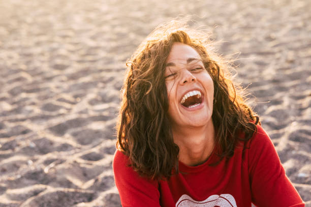 bright picture of laughing woman on the beach. backlight sunlight in background. beautiful young female model laugh like crazy. happiness and joyful concept for people in wanderlust stock photo