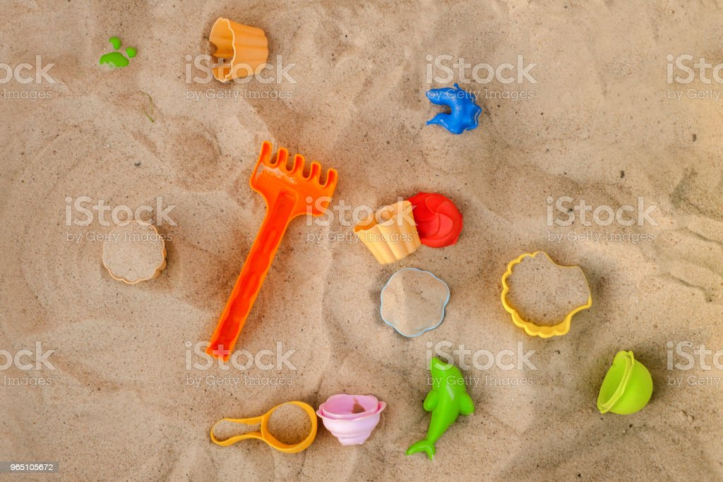 Bright plastic children's toy in the sand. Children's toys for the beach. Concept of beach recreation for children. Top view. Space for text. zbiór zdjęć royalty-free