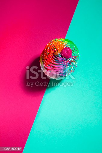 This is a photograph of a colorful sprinkled cupcake with a harsh shadow on a turquoise blue and red background and fits into the niche category of food pop art photography.