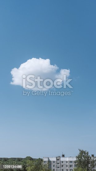 Bright blue sky with house and white cloud. Great background with copyspace. Nature background. Lifestyle and climate change concept. Vertical photo for stories.