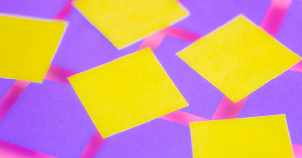 Bright purple blue paper squares with yellow square. Conceptual design, memo note with blank space, business ideas background. Grid pattern close up with pink background with shadows stock photo