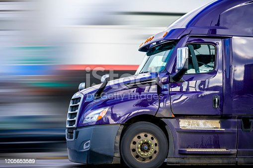 Bright Purple Bonnet Big rig long haul diesel Semi Truck with high cab configuration for improve aerodynamics transporting Commercial Cargo Driving on the Road for Delivery