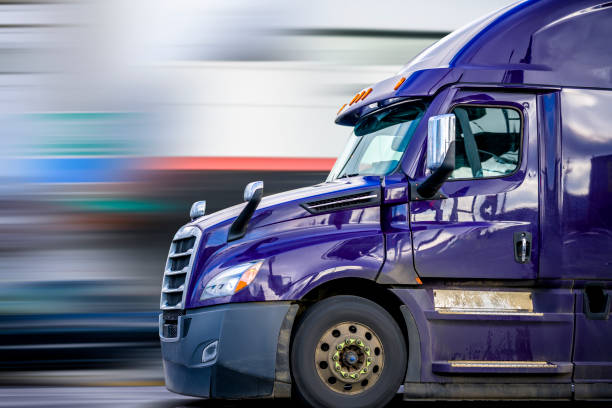 Bright Purple Bonnet Semi Truck Tractor with Reflection Driving on the Road for Delivery Commercial Cargo stock photo