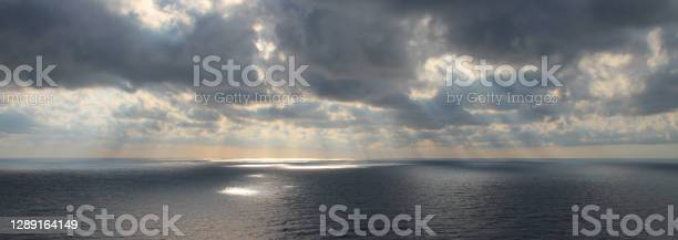 Photo of Bright rays of the sun through dramatic dark clouds over the sea, spots of light on the water, wide view.
