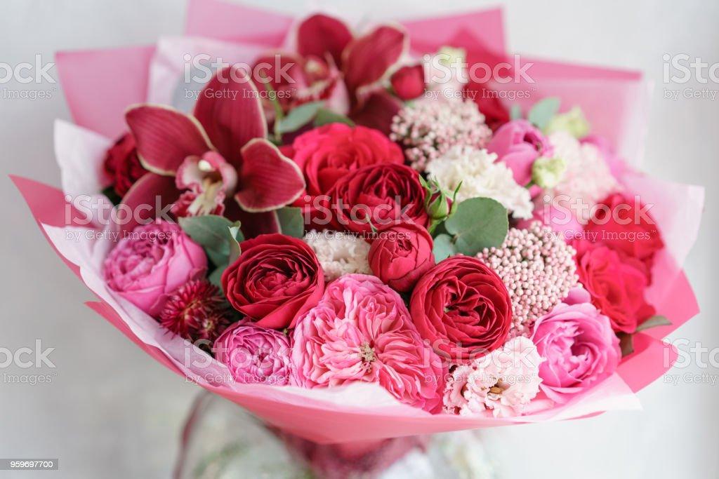 Helle rote Bouquet von Blumen auf Holztisch. Floristik-Konzept. Frühlings-Farben. die Arbeit der Floristen in einem Blumenladen. Vertikale Foto – Foto