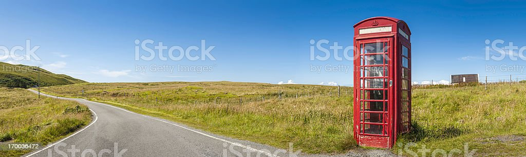 Bright red British telephone box in remote rural landscape panorama stock photo