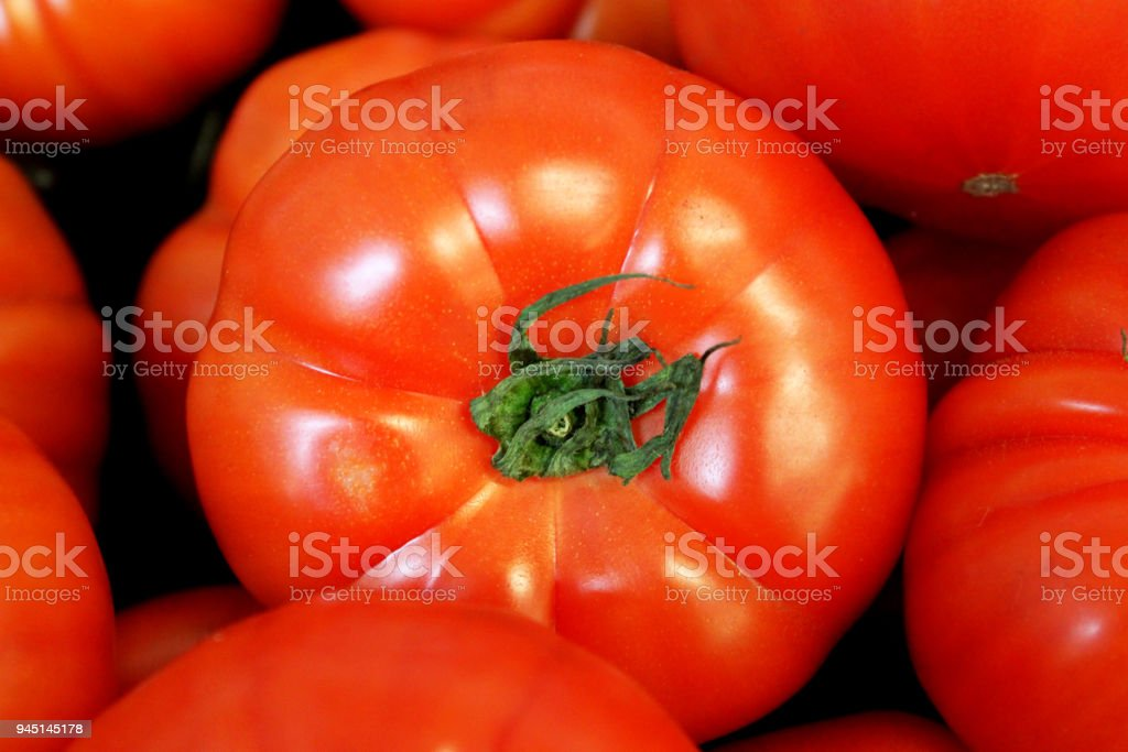 Bright red delicious tomato with green stem among other tomatoes stock photo
