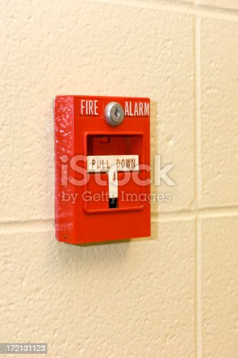 This fire-engine-red fire alarm stands ready to be pulled, alerting everyone in the building to the dangers of a fire.