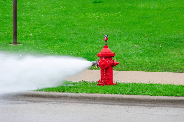 Bright red fire hydrant shooting out water at high pressure Hydrant flushing - public works maintenance fire hydrant stock pictures, royalty-free photos & images