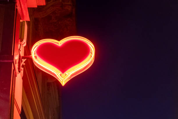 Bright red heart shaped illuminated neon sign stock photo
