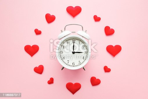 1139289535 istock photo Bright red hearts around white alarm clock on pastel pink background. Dating time. Love concept. Closeup. Top down view. 1186697017