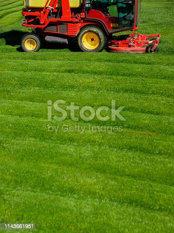 istock Bright red lawn mower on a freshly cut green grass 1143661951