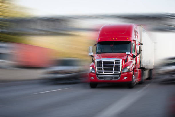Bright red modern big rig semi truck with semi trailer move with cargo on the highway - foto stock