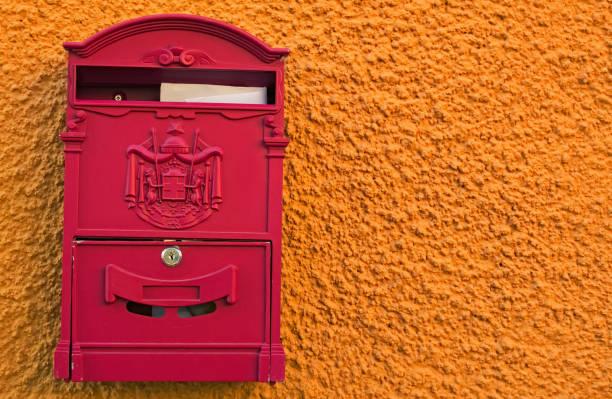 ein leuchtend roter briefkasten mit zwei weißen umschlägen an hellen gelb orange wand. loket, tschechien - buchstabentür kränze stock-fotos und bilder