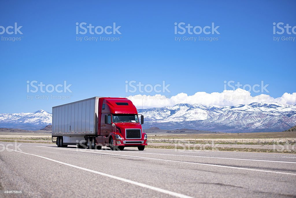 Bright red semi truck modern transportation on spectacular highway stock photo